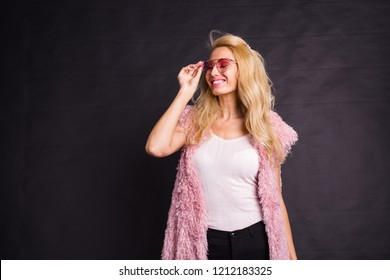 b4e0ea529d8 Fashion and people concept - young blonde woman in glasses standing in pink fur  coat and