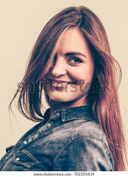 Fashion, people, jeans concept. Beautiful girl is smiling. Young woman is wearing denim shirt.