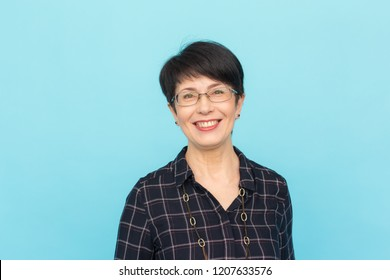 Fashion, people and style concept - Beautiful mid-aged woman wearing eye-glasses laughing on blue background