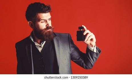 Fashion perfume bottle. Man perfume, fragrance. Bearded man holding up bottle of perfume. Masculine perfume. Male fragrance and perfumery, cosmetics.