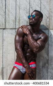 Fashion photo of african american athletic man in sunglasses with sport wet body, posing topless