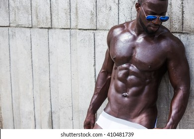 Fashion photo of african american athletic man with sport wet body posing near texture wall topless