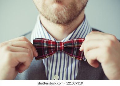 Fashion photo of a bearded man correcting his tie or bowtie. Party, costume wearing, businessman or gentleman concept. Male in vest and shirt correcting his colorful tie. High quality image