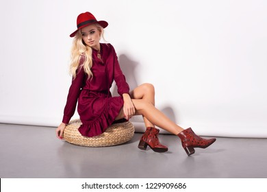 Fashion photo of a beautiful blonde young woman in a pretty dress, red hat holding handbag posing over white background. Fashion autumn summer photo. Hairstyle