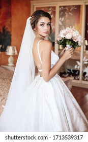fashion photo of beautiful bride with blond hair in elegant wedding dress with bouquet of flowers posing in room