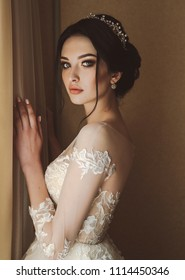 fashion photo of beautiful bride with dark hair in elegant wedding dress and diadem posing in room in the wedding morning