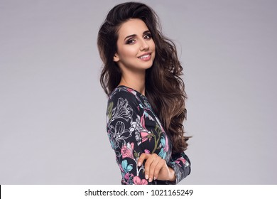 Fashion photo of a beautiful elegant young woman in a pretty dress with flowers holding handbag posing. Fashion spring summer photo