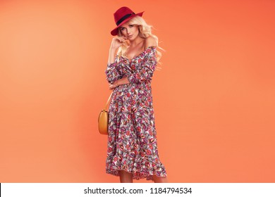 Fashion photo of a beautiful elegant young woman in a pretty dress with flowers, hat holding handbag posing over orange background. Fashion autumn summer photo
