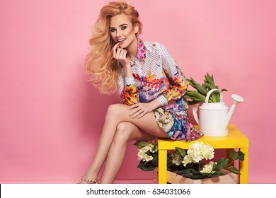Fashion photo of a beautiful elegant young woman in a pretty dress with flowers and watering can posing over pink background. Fashion photo. Sitting on yellow table.