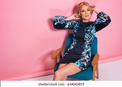 Fashion photo of a beautiful elegant young woman in a pretty blue dress with flowers posing over pink background. Fashion photo