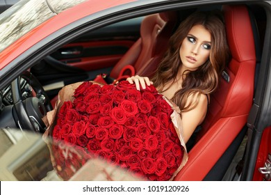 fashion photo of beautiful girl with dark hair in elegant dress posing in luxurious car with bouquet of red roses