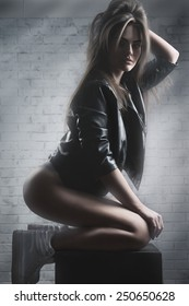 Fashion photo for beautiful girl sitting on table and posing in front of grey background