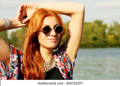 Fashion, photo of a beautiful red-haired model wearing a bright bohemian kimono, leather suede bag with fringe, black skirt and a T-shirt, round vintage sunglasses in a wooden frame. Boho chic style