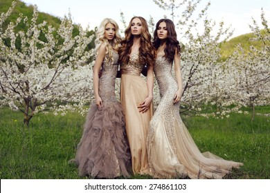 fashion photo of beautiful sensual women with dark hair in luxurious sequin dresses posing in spring blossom park