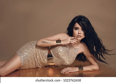 Fashion photo of beautiful sexy brunette woman with long blowing hair and golden jewelry. Female in luxurious glitter dress lying on beige studio background.