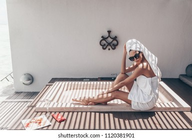 fashion photo of beautiful sexy girl  with white towel on her body and head relaxing on Maldive's villa outdoor bathroom