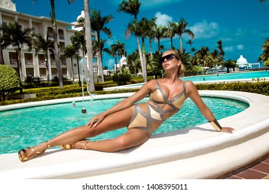 fashion photo of beautiful tanned woman with blond hair in elegant gold bikini relaxing beside a swimming pool - Image