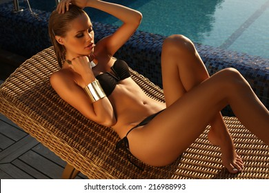 fashion photo of beautiful tanned woman with blond hair in elegant black bikini relaxing beside a swimming pool on wood wicker chair