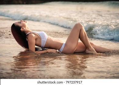 fashion photo of beautiful tanned woman with black hair in elegant white bikini relaxing on tropical island with perfect beach.