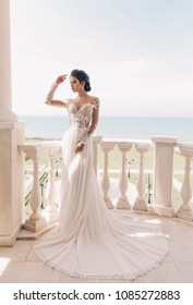 fashion photo of beautiful woman with dark hair in luxurious wedding dress posing outdoor
