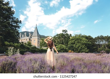 fashion photo of beautiful woman with dark hair in elegant dress and hat posing in flowering lavender field near antic castle