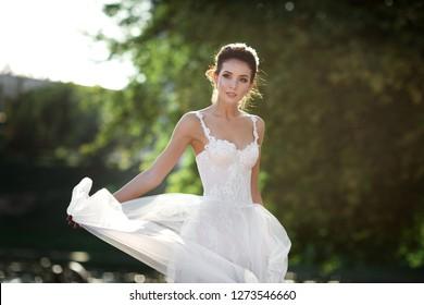 fashion photo of beautiful woman with dark hair in luxurious wedding dress posing outdoor.
