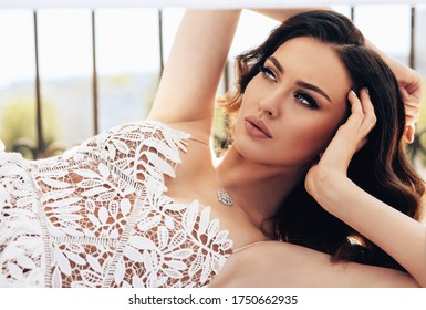 fashion photo of beautiful woman with dark hair in elegant dress with accessories posing in studio