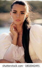 fashion  photo of beautiful woman with dark hair in luxurious white dress posing in beautiful landscape with sea view