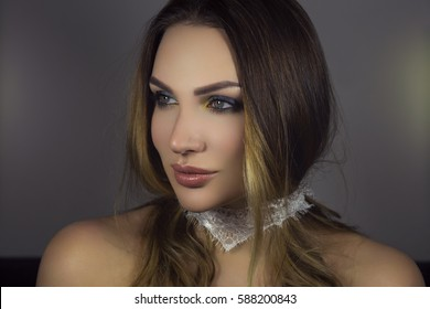 fashion photo of beautiful woman with dark hair and bright makeup, posing in studio
