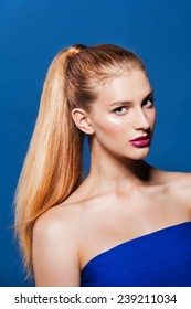 Fashion photo of beautiful woman with ponytail. Beauty woman on blue background