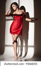 Fashion photo of beautiful woman in red nightdress in light of window