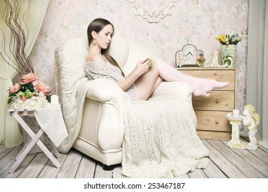 Fashion photo of beautiful woman sitting in armchair and reading a book