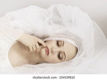 Fashion photo of beautiful woman under white veil.