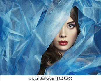 Fashion photo of beautiful women under blue veil. Beauty portrait