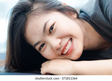 Fashion photo of beautiful young asian woman lying on the bed in condominium modern living