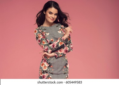 Fashion photo of a beautiful young brunette woman in a pretty dress with flowers posing over pink background. Fashion photo