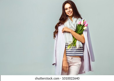 Fashion photo of a beautiful young woman with tulips in her hand .she dressed in a beautiful coat, scarf, pants and T-shirt with stripes.Spring concept. March 8. beautiful girl in stylish clothes