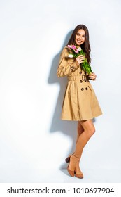 Fashion photo of a beautiful young woman with tulips in her hand .she dressed in a beautiful brown trench coat, crimson dress.Spring concept. March 8. white background; place for text
