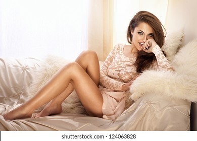Fashion photo of beautiful young woman wearing lace dress, relaxing and smiling in bright room, on the white couch.