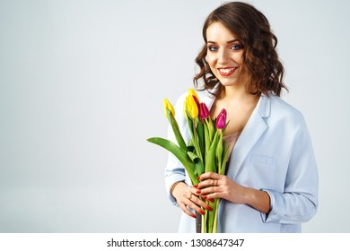 Fashion photo of a beautiful young woman with tulips in her hand. she dressed in a beautiful coat,  and T-shirt with stripes. Spring concept. March 8. beautiful girl in stylish clothes