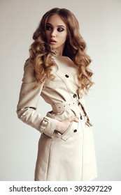 fashion photo of beautiful young woman with dark curly hair wears elegant spring coat,posing in studio