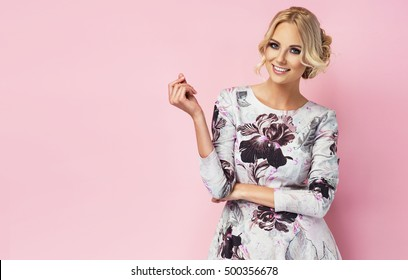 aef728013a8b Fashion photo of a beautiful young woman in a pretty dress with flowers  posing over pink