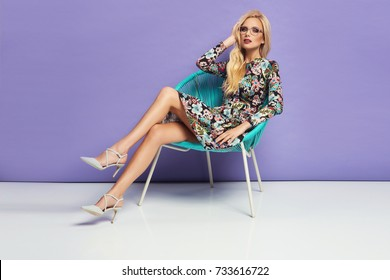 Fashion photo of a beautiful young woman in a pretty dress with flowers posing over purple background sitting on a turquoise chair.High heels shoes, fashionable glasses. Fashion spring autumn photo