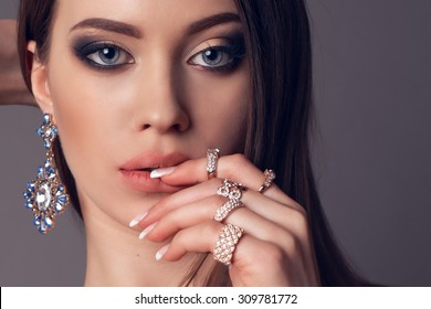 Fashion photo of elegant beautiful brunet woman with bright evening make up chick headdress and luxury jewelery posing at studio