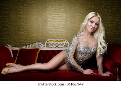 Fashion photo of elegant beautiful woman with blond hair in luxurious sequins dress indoors on red sofa