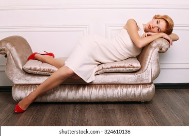 fashion photo of elegant and sexy red woman in white dress, red shoes with beautiful hairstyle lying on a luxurious couch and posing at studio with classic interior