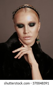 fashion photo of glamour beautiful woman with blond hair and smokey eyes makeup,wears luxurious fur coat, bijou and headband