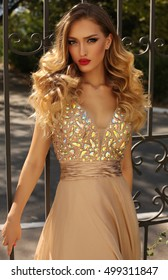 fashion photo of gorgeous woman with blond curly hair in luxurious sequin dress posing outdoor