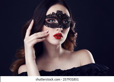 fashion photo of gorgeous woman with dark hair and blue eyes, with lace mask on her face,posing in dark studio