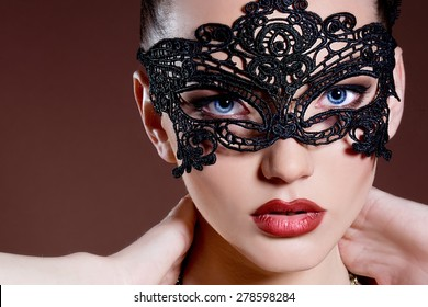 Fashion photo of gorgeous woman with dark hair and blue eyes, with lace mask on her face,posing in dark studio. Sexy Woman.